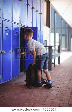 Full elngth of boy taking books from locker at school corridor