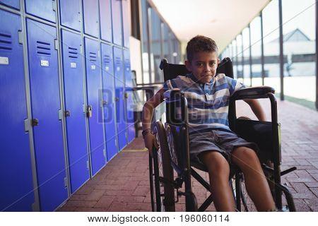 Portrait of boy sitting on wheelchair by lockers in corridor at school