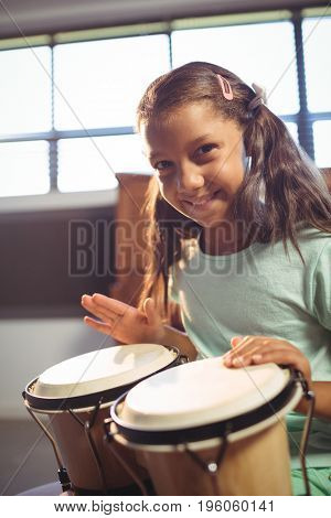 Portrait of smiling girl playing bongo drums in classroom at music school