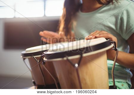 Mid section of girl playing bongo drums in classroom at music school