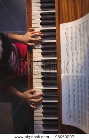 Overhead view of girl playing piano in classroom at music school