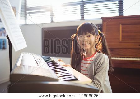 Portrait of smiling girl practicing piano in class at school