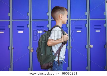 Side view of boy carrying backpack against lockers at school