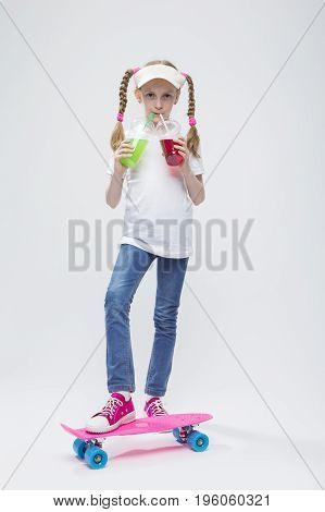 Kids Concepts. Portrait of Little Caucasian Blond Girl in Visor Posing on Pennyboard With Two Cups of Juice and Straw. Against White. Vertical Image Orientation