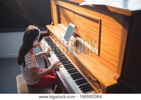 High angle view of concentrated girl wearing headphones while practicing piano in classroom at music school