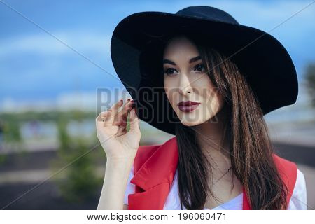Beautiful brunette woman in elegant hat and jacket over blue sky. Beauty, fashion outdoor.