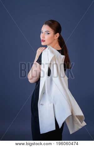 Fashion shot. Professional vogue model posing at studio. Collection of business clothes.