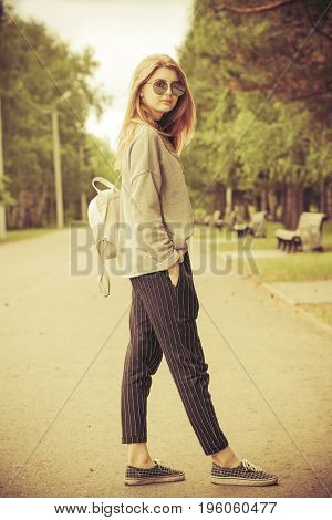 Teen style. Modern young girl with long blonde hair posing outdoor. Beauty, fashion.