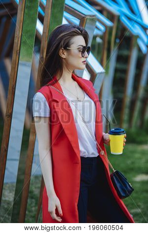 Outdoor summer portrait. Beautiful brunette woman in sunglasses standing with coffee at the street. Beauty, fashion outdoor.