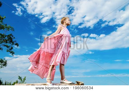 Happy little girl in beautiful long dress over blue sky. Children's fashion. Happy summer holidays.