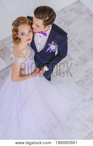 Loving bride and groom stand in tender embrace. Wedding fashion.