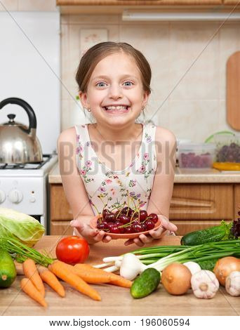 Girl giving a plate of cherries. Many fruits and vegetables on the table in home kitchen interior, healthy food concept