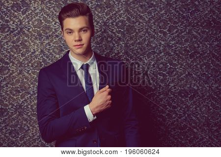 Handsome young man in elegant suit posing over vintage background. Business style. Male beauty, fashion. Hairstyle.