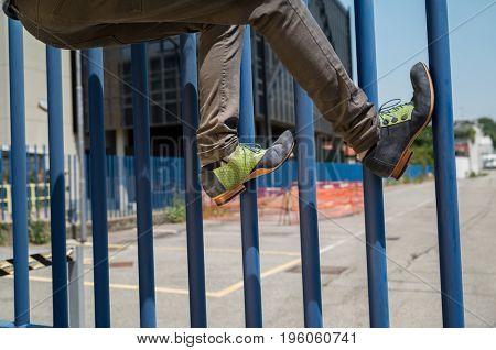 Detail of feet crossing a blue gate