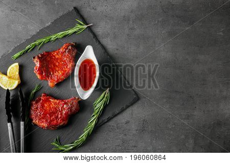Delicious pork ribs with tomato sauce, rosemary and lemon on table