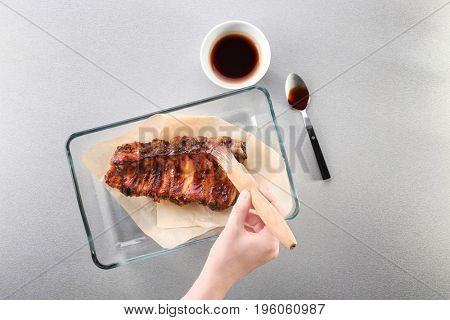 Woman adding soy sauce to roasted pork ribs in baking tray on table