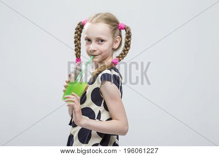 Cute And smiling Caucasian LIttle Girl With Pigtails Posing in Polka Dot Dress with Cup of Greeen Juice. Drinking Through Straw. Horizontal Image Orientation