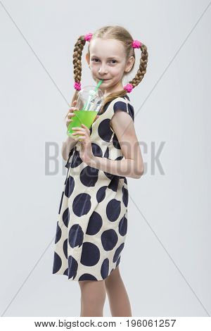 Portrait Of Cute And smiling Caucasian LIttle Girl With Pigtails Posing in Polka Dot Dress with Cup of Greeen Juice. Drinking Through Straw. Vertical Image Orientation