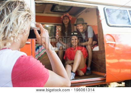 Man photographing happy friends through camera sitting in camper van