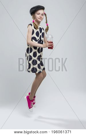 Portrait of Jumping Caucasian Girl With Pigtails Posing in Gray Velvel Cap and Polka Dot Dress with Cup of Red Juice. Drinking Through Straw. Against White. Vertical Shot