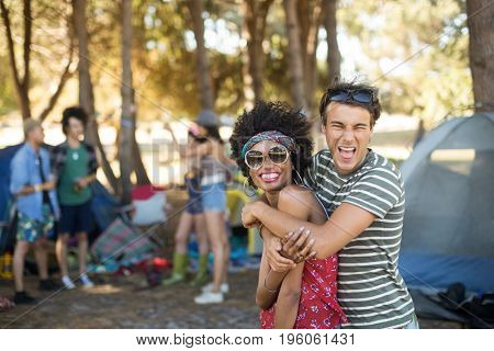 Portrait of cheerful young friends embracing at campsite
