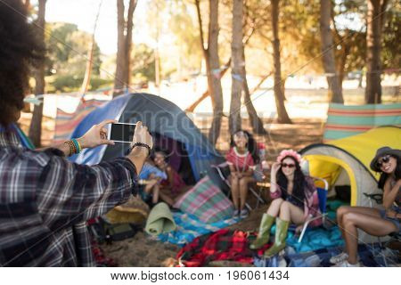 Man photographing smiling friends through mobile phone at campsite