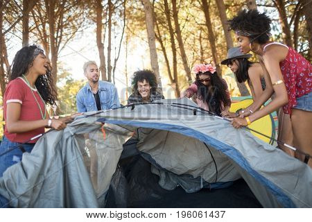 Happy young friends setting up tent at countryside