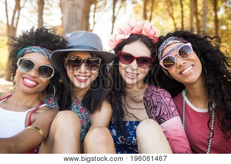 Portrait of smiling female friends sitting together at campsite
