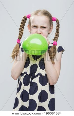 Portrait of Funny Caucasian Blond Girl With Pigtails Posing in Polka Dot Dress Against White. Blowing Up Green Heart Shaped Air Balloon. Vertical Image Composition
