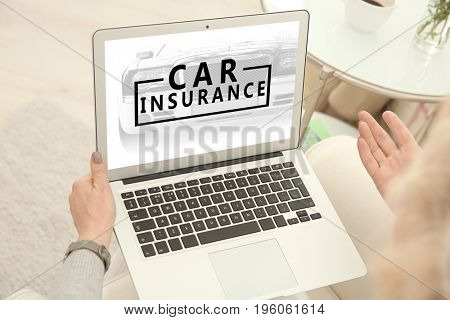 Woman using laptop at home. Car insurance concept