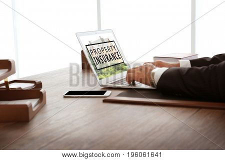 Man using laptop in office. Property insurance concept