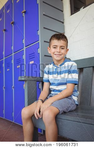Portrait of smiling boy sitting on bench by lockers in corridor at school
