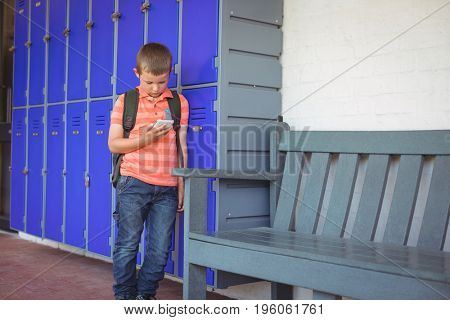 Boy using mobile phone while leaning on lockers in corridor at school