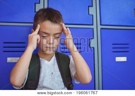Boy suffering from headache against lockers at school