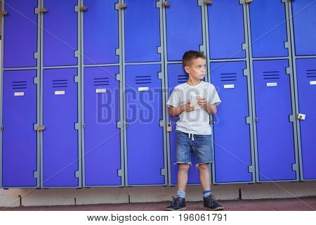 Boy looking away while using mobile phone against lockers at school