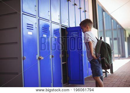 Side view of boy standing by open locker in corridor at school