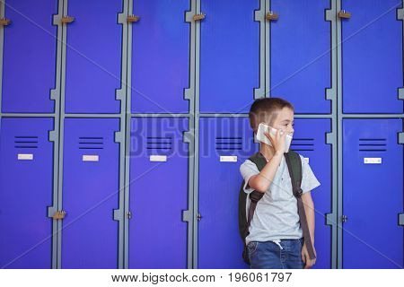 Elementary boy talking on mobile phone while standing against lockers at school
