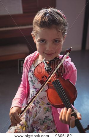 Portrait of girl student rehearsing violin in music class