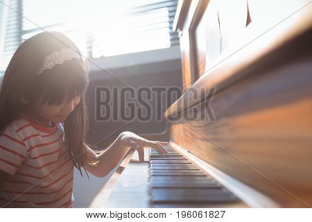 Elementary girl practicing piano in class at music school