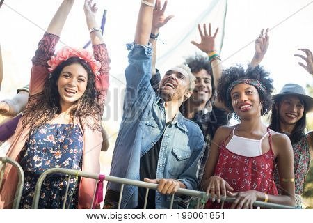 Low angle view of happy friends with arms raised enjoying during music festival