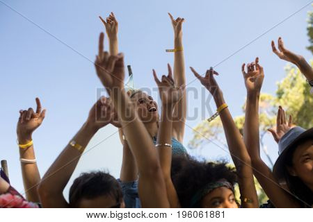 Low angle view of cheerful woman by fans with arms raised enjoying at music festival