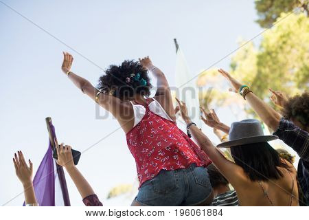 Tilt image of friends with arms raised against sky enjoying at music festival