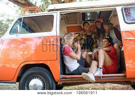 Low angle view of happy friends sitting together in camper van