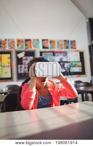 Surprised girl using virtual reality glasses in classroom at school