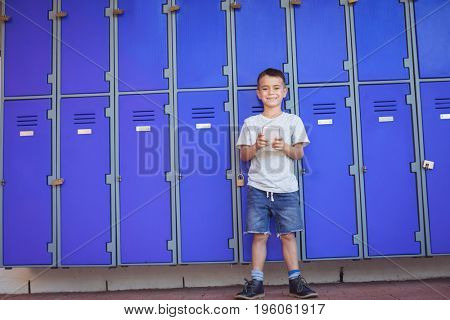 Portrait of smiling boy using mobile phone while standing against lockers at school