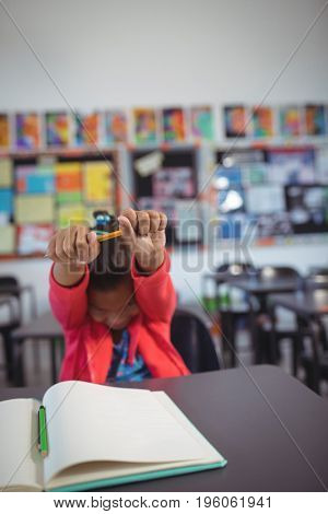 Girl stretching hands while sitting at desk in classroom