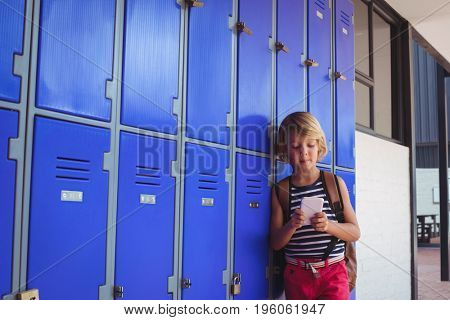 Schoolboy using mobile phone while standing by lockers in corridor at school