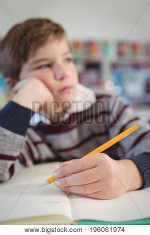 Thoughtful elementary schoolboy studing while sitting at desk at classroom