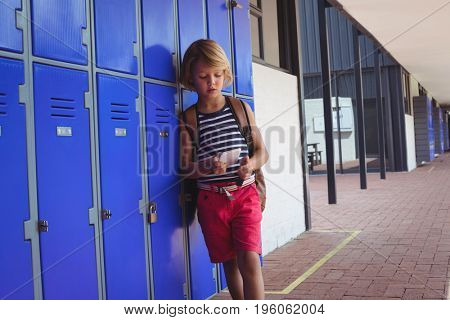 Boy using mobile phone while standing by lockers in corridor at school