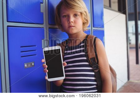 Portrait of boy holding mobile phone while standing by lockers in corridor at school
